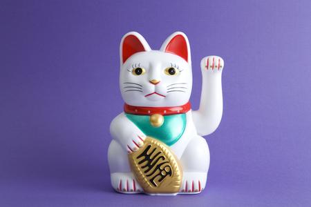 eine Maneki-neko Plastikkatze, symbolisiert Glück und Reichtum, auf einem Pop und bunten Hintergrund. Minimales Farbfoto