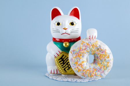 a maneki neko presenting a multicolor donuts on a doily paper and a pop colorful background. Minimal quirky color still life photography