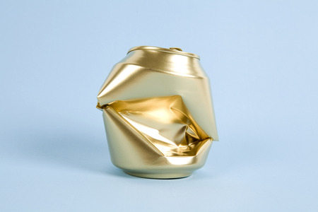 a crushed can of soda painted in gold on a colorful background. Minimal color still life and quirky photography Stock Photo