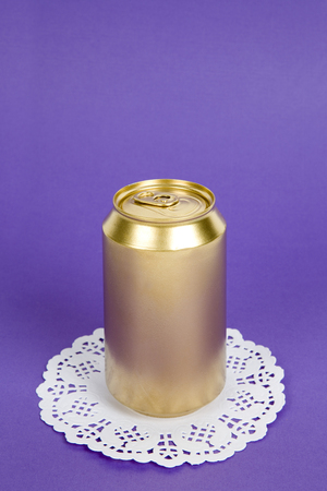 an unused can painted in gold on a virant colored background. Minimal color still life and quirky photography