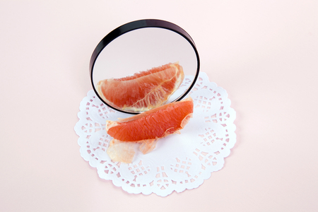 poetic: Minimalist and poetic composition of a grapefruit reflected in a mirror. Minimal color still life photography Stock Photo