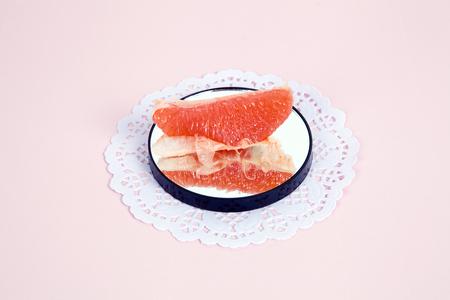 グレープ フルーツのミニマリストと詩的な組成は、鏡に映る。 最小限の色のある静物写真