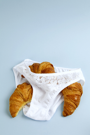 A french croissant in a panties. Pastel blue background. Minimal color and absurd still life photography