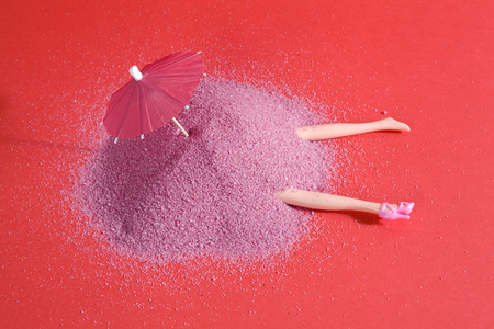 Arm and legs doll emerging from a pile of pink sand as if it were hiding. Minimal funny and quirky design still life photography