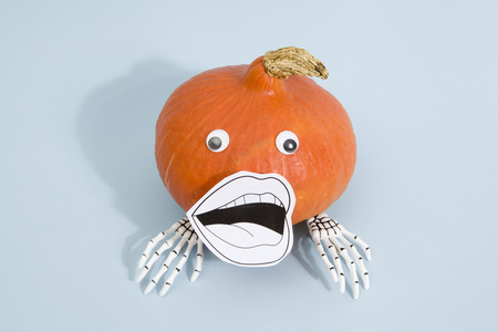 Composition of a pumpkin with skeleton hand wearing a paper drawn mouth and dolls eyes on a pop vibrant blue background. Minimal color still life photography