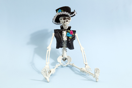 Mexican skeleton celebrating el dia de los muertos on a blue vibrant pop background. Minimal color still life photography