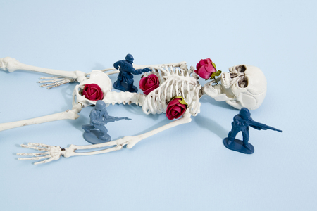 plastic soldier: Plastic toy Soldiers arround a pop skeleton wearing flower roses on a pop vibrant blue background. Minimal color still life photography Stock Photo