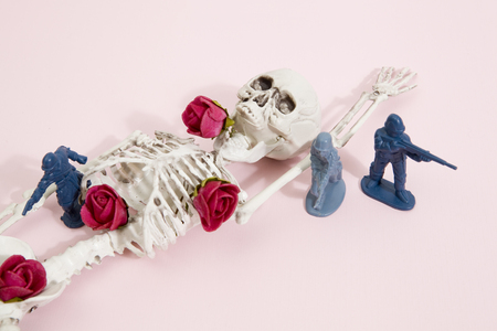 plastic soldier: Plastic toy Soldiers around a pop skeleton wearing flower roses on a pop vibrant pink background. Minimal color still life photography