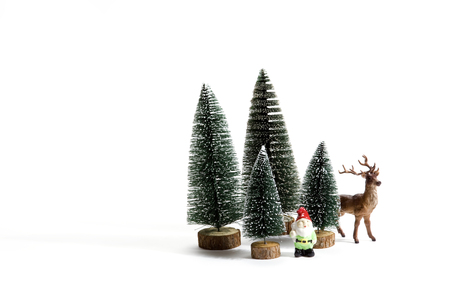 dwarf christmas: Isolated group of full artificial firs like a small forest tree in a ceramic pattern plate with a figurine reindeer and garden gnome beside on a white background. Minimal still life photography