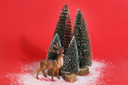 Isolated group of full artificial firs like a small snowy forest tree with a figurine reindeer inside on a vibrant red background. Minimal still life photography