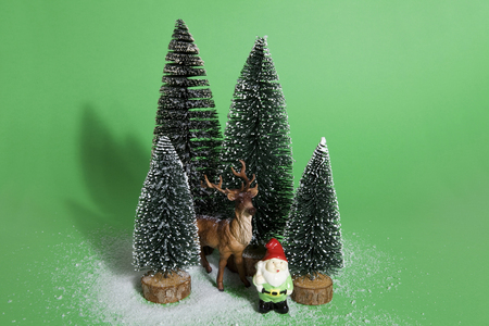 Isolated group of full artificial firs like a small forest tree in a ceramic pattern plate with a figurine reindeer and garden gnome beside on a green background. Minimal still life photography Stock Photo