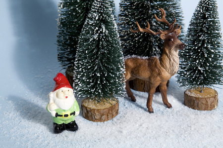 dwarf christmas: Staging of full artificial firs like a small snowy forest tree with a figurine reindeer inside and a garden gnome beside on a vibrant blue background. Minimal still life photography Stock Photo