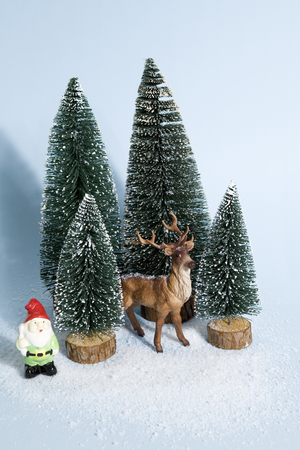 Staging of full artificial firs like a small snowy forest tree with a figurine reindeer inside and a garden gnome beside on a vibrant blue background. Minimal still life photography Stok Fotoğraf