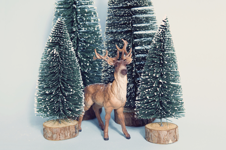 Vintage photography filtered of Staging of full artificial firs like a small snowy forest tree with a figurine reindeer inside on a vibrant blue background. Minimal still life photography
