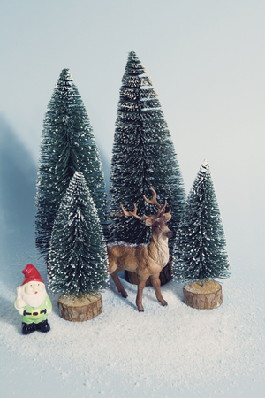 Vintage photography filtered of Staging of full artificial firs like a small snowy forest tree with a figurine reindeer inside and a garden gnome beside on a vibrant blue background. Minimal still life photography
