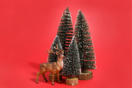 Isolated group of full artificial firs like a small forest tree with a figurine reindeer inside on a vibrant red background. Minimal still life photography