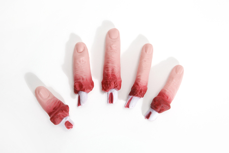 5 fake bloodied plastic fingers as if they had been torn off on a white background. reconstituted hand. Minimal still life photography Stock Photo