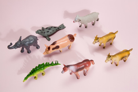 different plastic figurine toys like animals herd on a vibrant pink background. Minimal still life photography Stock Photo