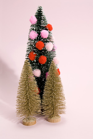 isolated christmas tree decorated with pompoms instead of christmas ball and gold firs. Minimal still life photography