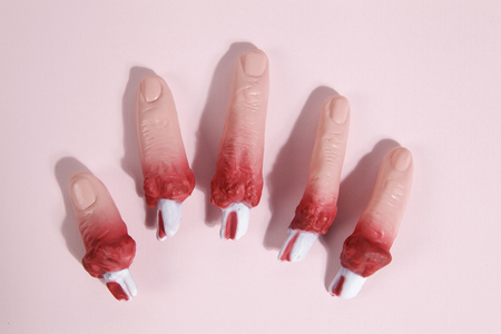 5 fake bloodied plastic fingers as if they had been torn off on a vibrand pink background. Gradient colors. Minimal still life photography