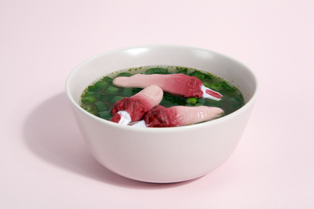 a fingers meat broth with scallions floating on the surface of the soup in a pink bowl. Gradient color. Minimal and quirky photography. Stock Photo