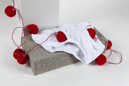 a red pompon light string inside a y fronts underwear placed on a cinder block. White background. Minimal funny and quirky pop still life photography