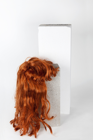A red wig put on a gray cinderblock, on a white background. Minimal funny and quirky design still life photography