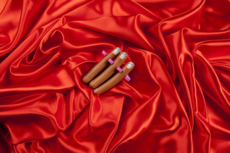 3 sausages with false nails placed in a manicure spacer like fingers on a vibrant red satin background. Minimal funny and quirky pop still life photography
