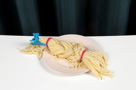 a delicious italian buttered spaghetti meal presented in a pink plate as blond braided hair. Minimal funny and quirky pop still life photography