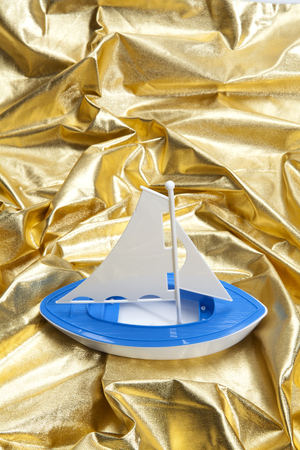 a plastic toy boat sailing in a gold fabric choppy waters. Luxury composition. Minimal color still life photography.