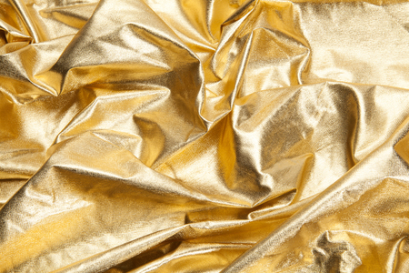 close-up view of a gold piece of fabric like ripples. Luxury composition. Minimal color still life photography. Minimal color still life photography Stock Photo