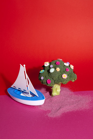a standing broccoli covered with numerous plastic flowers like a tree with a plastic toy boat beside on pink sand representing a desert island. Vibrant pink and red background. Humorous metaphor. Minimal color still life photography Stock Photo