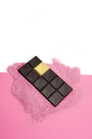 a whole dark chocolate bar with a gold square. Metaphor of luck. Minimal color still life photography. Stock Photo