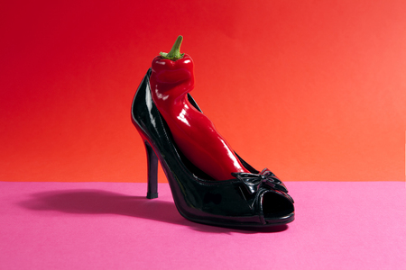 a vibrant red pepper inside a black varnished shoe with a bow on red and pink background. Absurd composition. Minimal quirky color still life photography.