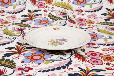 a flower plate hidden on a flowery fabric. Camouflage game. Minimal color still life photography.