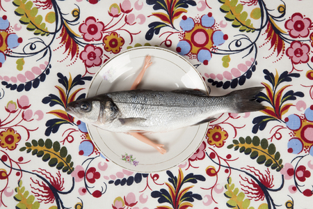 A bass fish with arms doll inside a flower plate hidden on a flowery fabric. Camouflage game and anthropomorphism. Minimal color still life photography.