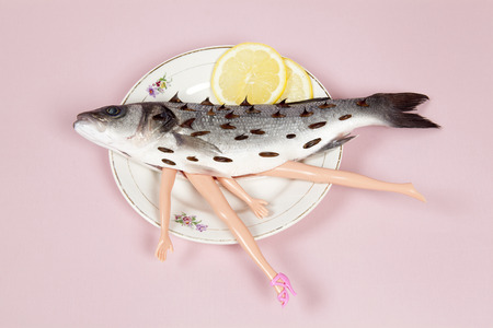 A bass fish with arms and legs of a doll inside on a flower plate. Cannibalism and anthropomorphism on a pink feminine background. quirky minimal color still life photography.  Stock Photo