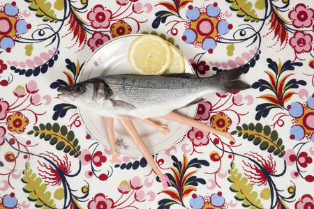 A bass fish with arms and legs of a doll inside on a flower plate