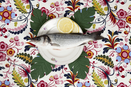 A bass fish and slice of lemon inside a flower plate hidden on a flowery fabric and four monstera deliciosa leaves. Camouflage game. Minimal color still life photography.