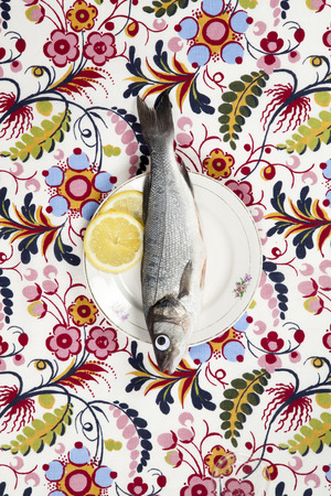 A bass fish with eyes doll inside a flower plate hidden on a flowery fabric. Camouflage game. Minimal color still life photography.