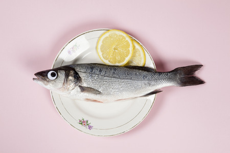 A bass fish with eyes doll inside a flower plate hidden on a pop pink background. Minimal quirky color still life photography. Stock Photo