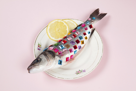 A bass fish covered with colorful precious stones inside a flower plate hidden on a pop pink background. Minimal quirky color still life photography.