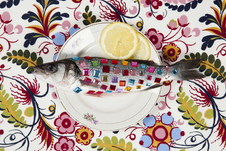 A bass fish covered with colorful precious stones inside a flower plate hidden on a pop floral patterned fabric background. Minimal quirky color still life photography.
