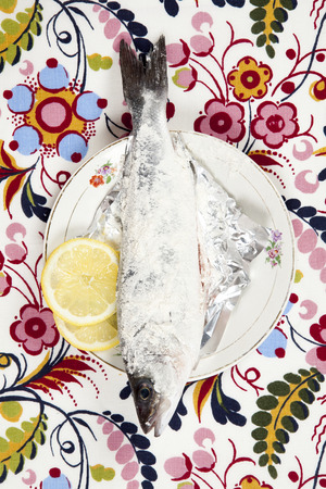 A preparation of a bass fish with a slice of lemon beside inside a flower plate hidden on a flowery fabric. Camouflage game. Minimal color still life photography.