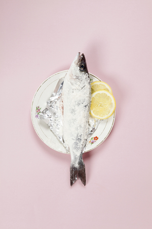 A preparation of a bass fish with a slice of lemon beside inside a flower plate hidden on a pop pink background. Minimal color still life photography.