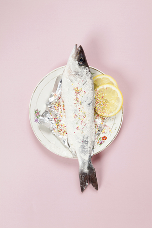 A preparation of a bass fish with sprinkles and a slice of lemon beside inside a flower plate hidden on a pop pink background. Minimal color still life photography.