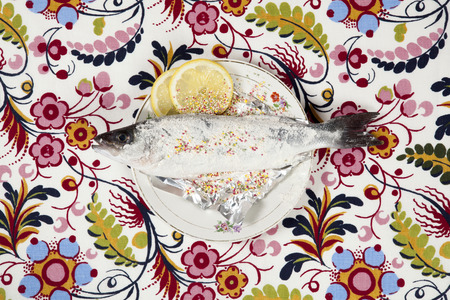 A preparation of a bass fish with sprinkles and a slice of lemon beside inside a flower plate hidden on a flowery fabric. Camouflage game. Minimal color still life photography.