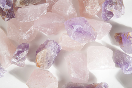 several pieces of raw amethyst and pink quartz like a pile on a white background. Minimal color still life photography.