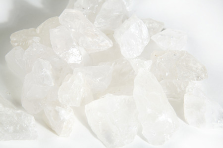 Pile of several pieces of rock crystal also called ice crystal or clear crystal on a white background. Minimal color still life photography. Stock Photo