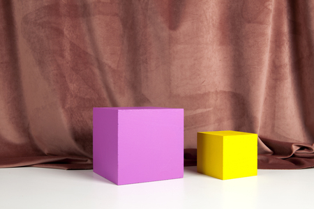 Two bright yellow and pink cubes in front of an old pink velvet curtain. Minimal color still life photography.